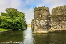 Castles of King Edward in Gwynedd - The Castles and Town Walls of King Edward in Gwynedd: The outer curtain wall and the moat of Beaumaris Castle. The castle has two gates, the...