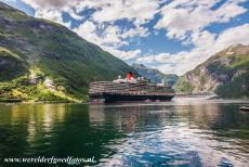 Geirangerfjord and Nærøyfjord - West Norwegian Fjords: The huge Queen Elizabeth cruise ship in the Geirangerfjord. The fjord is surrounded by some of the steepest mountains...