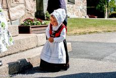 Church Village of Gammelstad, Luleå - Church Town of Gammelstad, Luleå: A child dressed in Swedish traditional costume in front of the Nederluleå Church during...